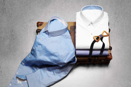 Composition of stylish mens shirts with wooden yellow bow tie on a retro suitcase.