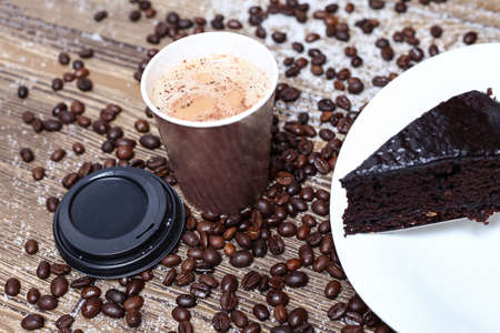 Paper cup of espresso coffee with Chocolate brownie cake and coffee  beans in the background.