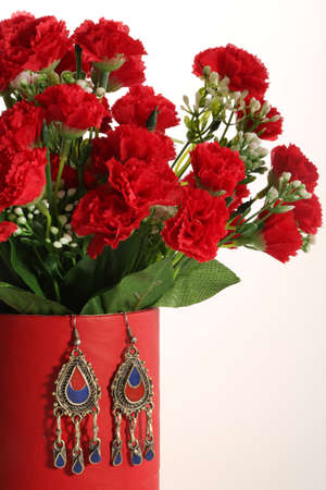Beautiful set of flowers and earrings in oriental style hanging on a red vase