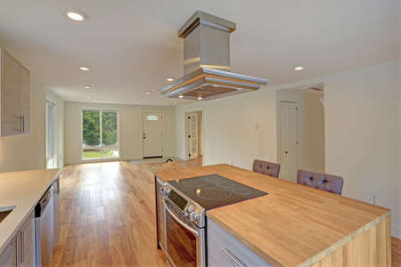 stainless: Newly remodeled kitchen boasts kitchen island with a hood, gray Shaker cabinets, quartz counters and modern stainless steel appliances.