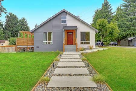 Pasarela de hormigón con guijarros conduce a una casa unifamiliar moderna que ofrece un pequeño porche con una puerta de entrada roja.