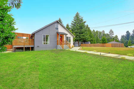 renovated: Nicely renovated grey and white home exterior with grass filled front yard. Stock Photo