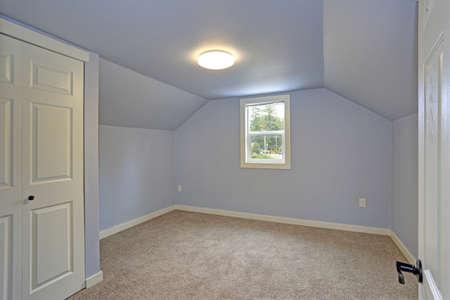 Small empty blue bedroom accented with vaulted ceiling, soft carpet floor and a small window. Renovated modern home interior, Everett, WA. Stock Photo