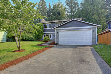 Lovely grey rambler house exterior features grey siding accented with white moldings, attached garage with asphalt driveway and well manicured front yard. Kirkland, WA, USA. 新闻类图片