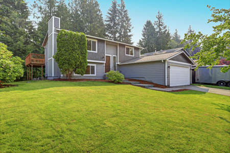 Lovely grey rambler house exterior features grey siding accented with white moldings, attached garage with asphalt driveway and well manicured front yard. Kirkland, WA, USA. Editorial