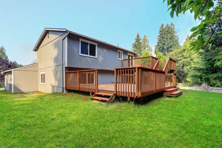 Backyard view of grey rambler house with upper and lower decks and green lawn. Kirkland, WA, USA. Banque d'images - 144812922