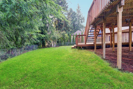 Backyard view of grey rambler house with upper and lower decks and green lawn. Kirkland, WA, USA. 免版税图像 - 144812923