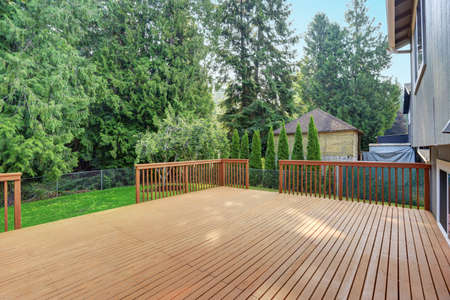 Empty walkout deck boasts redwood railings overlooking well kept back yard. 免版税图像