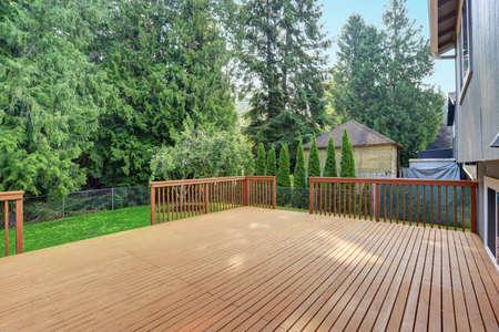 Empty walkout deck boasts redwood railings overlooking well kept back yard. Standard-Bild