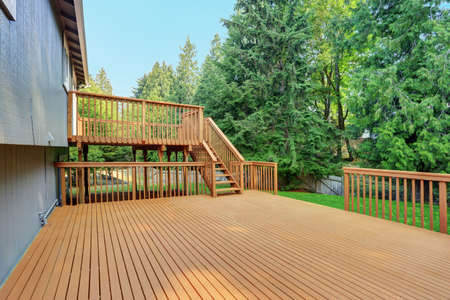 Backyard view of grey rambler house with upper and lower decks and green lawn. Kirkland, WA, USA.