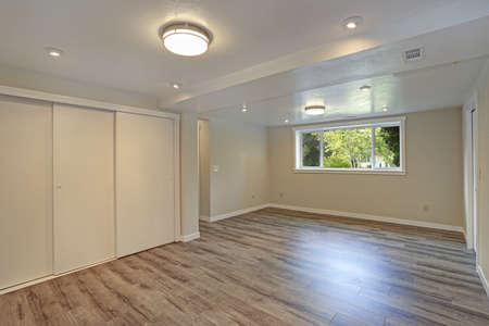 Bright Beige Large Empty Room With Hardwood Floor, Built In Closet, Small  Window