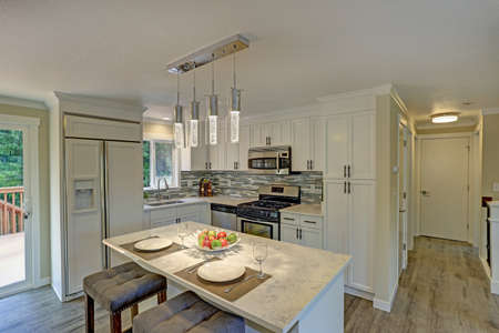Beautiful open plan second floor white kitchen with traditional style kitchen cabinetry, mosaic backsplash, a bar island illuminated by modern glass light pendants and a built-in refrigerator.
