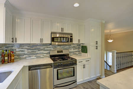 Beautiful open plan second floor white kitchen with traditional style kitchen cabinetry, mosaic backsplash, a bar island and modern stainless steel appliances.