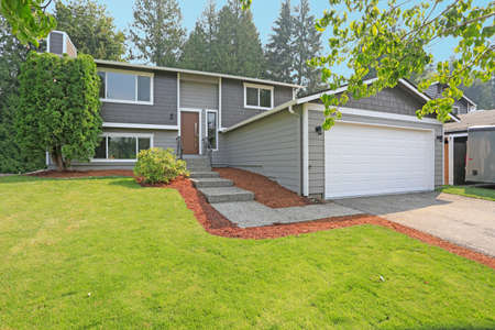 Lovely grey rambler house exterior features grey siding accented with white moldings, attached garage with asphalt driveway and well manicured front yard. Kirkland, WA, USA.