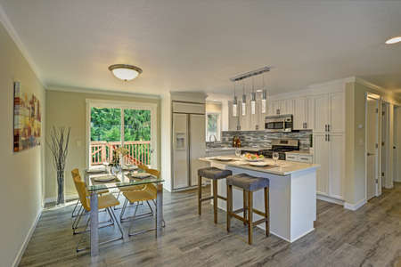 open floor plan: Beautiful open plan second floor white kitchen with dining space. Traditional style kitchen cabinetry, mosaic backsplash, a bar island and a modern glass top dining table with yellow chairs.