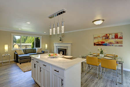 Beautiful open plan second floor living room, kitchen and dining space. Kitchen boasts a bar island illuminated by modern glass pendants facing a glass top dining table with yellow chairs.