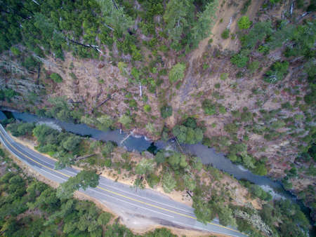 forested: Aerial view of Mountain road with forested hills, fire burned dead trees along a narrow river. Stock Photo
