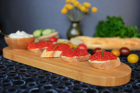Close up of four sandwiches with red caviar on a wooden cutting board. Light snack.
