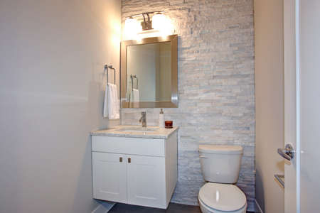 Contemporary white and gray bathroom features stone accent wall framing a white bathroom vanity under a silver beveled mirror illuminated by double sconces. Редакционное