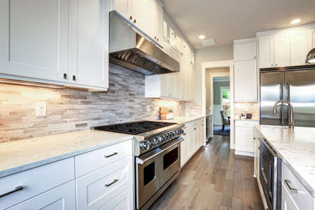 Amazing white kitchen design with white shaker cabinets paired with  white and gray marble counters, large White kitchen peninsula and high-end stainless steel appliances. 免版税图像 - 88790478