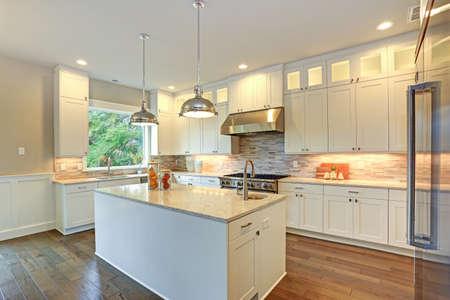 Conception étonnante de cuisine blanche avec des armoires à shaker blanches jumelées avec des comptoirs en marbre blanc et gris, une grande péninsule de cuisine blanche et des appareils électroménagers haut de gamme en acier inoxydable.