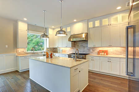 El increíble diseño de la cocina blanca con gabinetes de coctelera blanca combinados con mostradores de mármol blanco y gris, la gran península de cocina blanca y los electrodomésticos de alta gama de acero inoxidable. Foto de archivo - 88790479