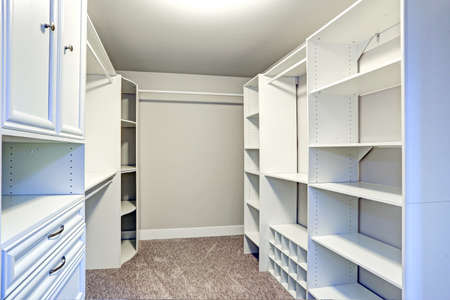 Narrow walk-in closet lined with built-in drawers, clothes rails and shelving over brown carpet floor.