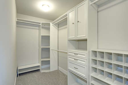 Narrow Walk In Closet Lined With Built In Drawers, Clothes Rails And  Shelving