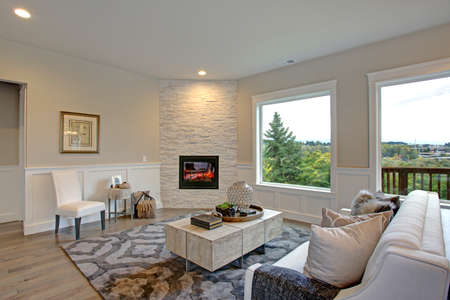 Relaxing white living room features corner stone fireplace lined with tan walls accented with lower wall white wainscoting framing large windows with gorgeous view.