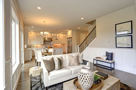 Relaxing white living room in a luxury new construction home features soft colored tan walls accented with lower wall white wainscoting, white tufted sofa with pillows and wooden cocktail table.
