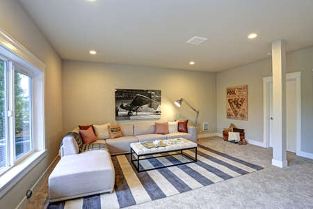 Light entertainmentgame room design in a luxury new construction home showcases soft beige sectional with red pillows offering comfortable seating atop a white and blue striped rug.