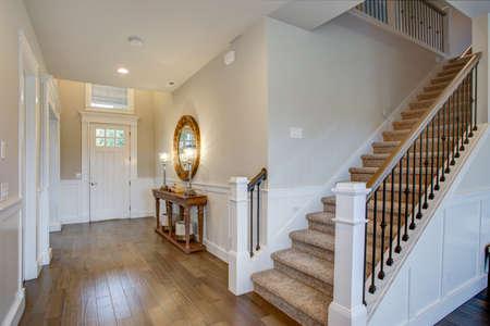 Fabuleux hall d'entrée avec un mur d'escalier orné de planche et de lattes et équipé d'une console en bois illuminée par des lampes de fer.