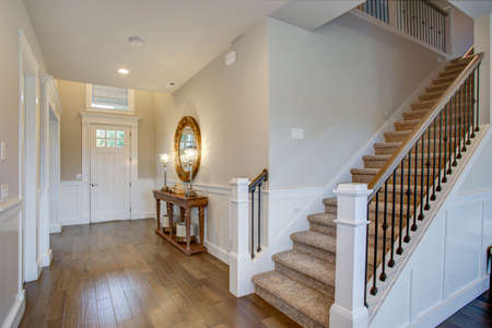 Fabulous foyer features staircase wall adorned with board and batten and fitted with a wood console table illuminated by iron buffet lamps.