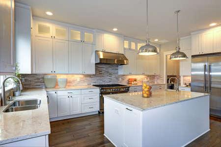 흰색과 회색의 대리석 카운터와 싱크대가있는 커다란 흰색 주방 반도, 싱크대가있는 커다란 흰색 부엌 반도, 경목 주방 바닥.