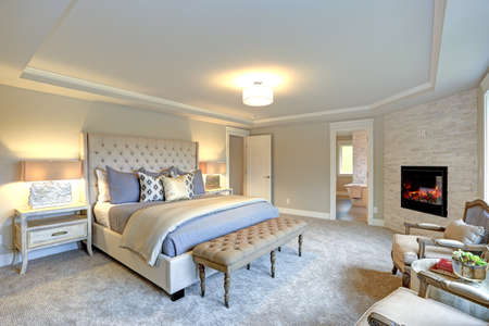 Luxury master bedroom interior furnished with two nightstands topped with stone and brass lamps, Large ivory cream tufted upholstered headboard bed and a tufted bench at the foot of the bed. Stock Photo