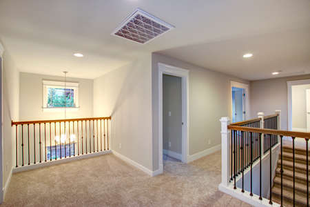 Empty New construction home interior features second floor landing with light grey walls paint color, beige carpet floor and a staircase.