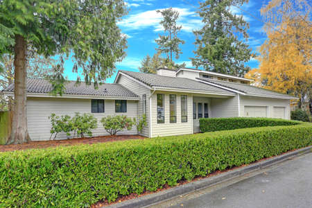Nicely remodeled home exterior with boxwood hedge plus two garage spaces.