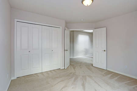 Empty bedroom interior with carpet floor, white walls and built-in closet.