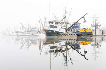 SEATTLE, WA - OCTOBER 28, 2017: Fishing Boats reflected on the Puget Sound waters and Docked at Fishermens Terminal in Seattle on a foggy morning.