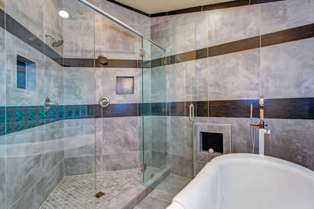 Stunning bathroom boasts an oversized glass shower and white freestanding tub lined with gray marble tiled surround accented with black tiled stripes.  Archivio Fotografico