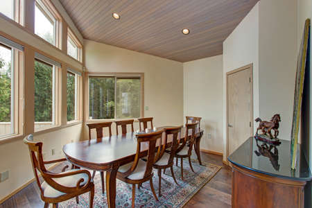 Chic dining room features white ceiling over a wood dining table surrounded by beige upholstered wood dining chairs atop a rug.