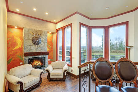 Warm cozy family room with of a luxury mansion house. Cream walls accented with brown trim paired with antique wood carved armchairs placed in front of stone fireplace.  版權商用圖片
