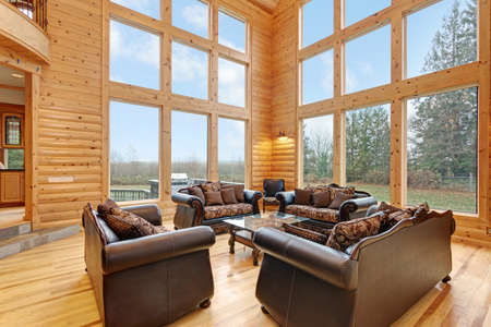 Spacious great room features pine paneled walls, Two-Story Windows and furnished with luxurious brown leather sofas.