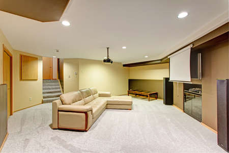 Beige basement movie room features a leather sectional under a ceiling mounted movie projector.
