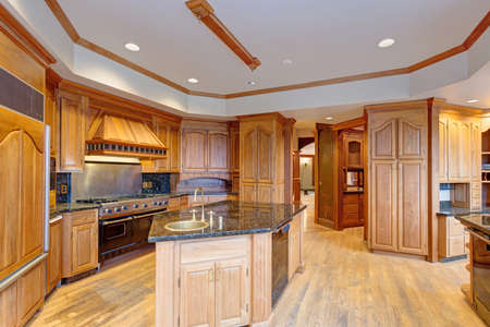 Gorgeous light filled mansion features an opulent kitchen with rich wood cabinetry with marble countertops and an oversized kitchen  island.