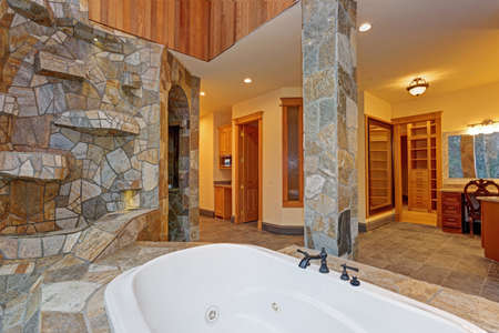 Luxurious mansion bathroom features Drop-In Bathtub paneled in stone tiles, natural Stone columns, amazing walk-in shower with arch doorway and makeup vanity.