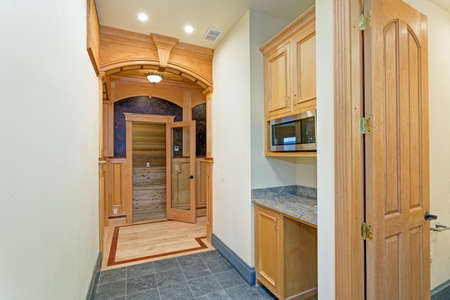 Bright mansion hallway interior with wet bar nook boasting light wood cabinets and granite countertop.