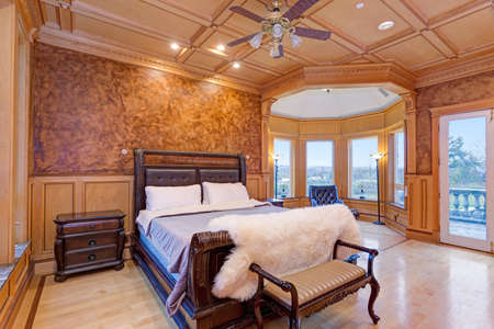 Welcoming mansion bedroom features a rustic wood coffered ceiling over a brown carved wood master bed topped with a fluffy sheepskin cover, reading nook filled with tons of natural light.