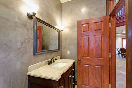 Luxury Mansion Interior Features New Bathroom With Grey Stucco Walls, Rich  Brown Bathroom Vanity Topped
