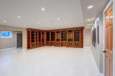 Spacious empty basement area with large custom built bookcase. Luxury lifestyle in a stunning wedding venue.  Foto de archivo